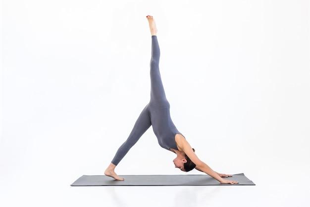 Femme faisant du yoga sur le tapis en studio sur fond blanc