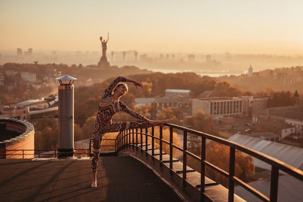 Femme faisant du yoga sur le toit d'un gratte-ciel dans la grande ville
