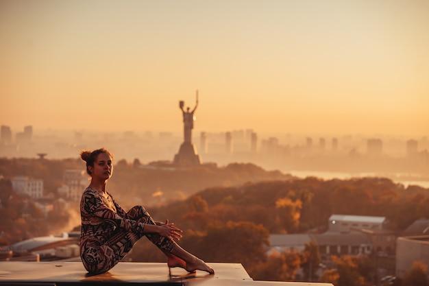 Femme faisant du yoga sur le toit d'un gratte-ciel dans la grande ville.
