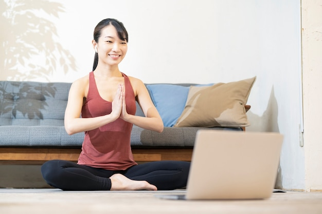 Une femme faisant du yoga tout en regardant l'écran de l'ordinateur dans la chambre