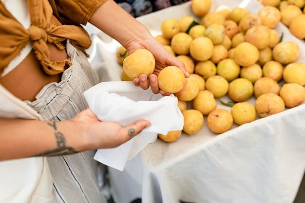 Femme faisant des emplettes pour l'abricot, achetant au marché frais de fruits