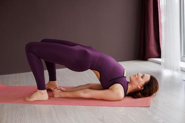 Femme faisant des étirements journée internationale du yoga. asana setu bandha sarvangasana