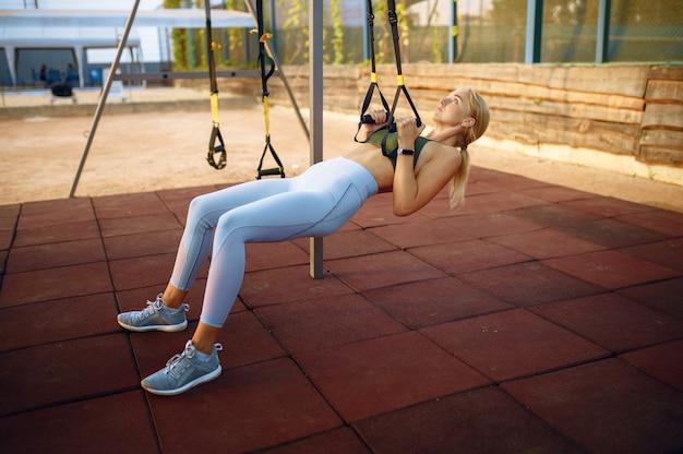 Femme faisant de l'exercice avec des cordes sur un terrain de sport à l'extérieur