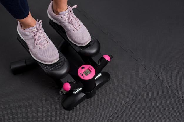 Femme faisant de l'exercice sur machine pas à pas. photographie en gros plan des pieds avec espace de copie pour le texte.