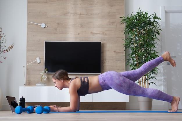 Femme faisant de l'exercice à la maison devant son ordinateur portable étirant le concept de yoga et de remise en forme