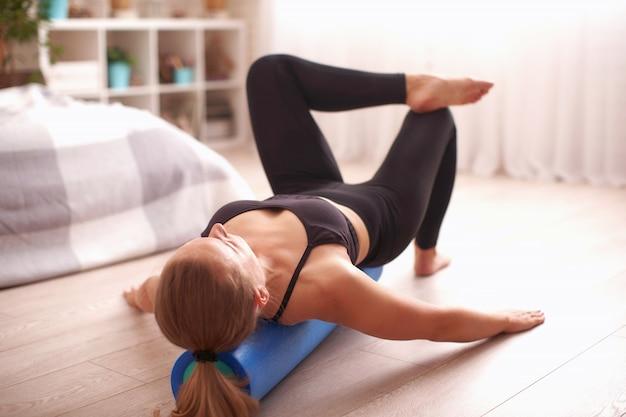 Femme faisant de l'exercice avec un rouleau