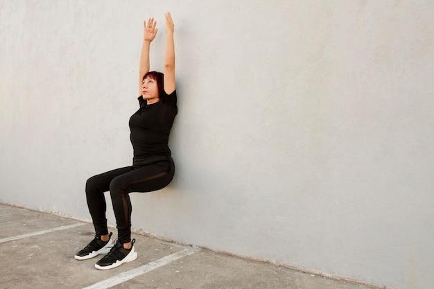 Femme faisant l'exercice de support mural