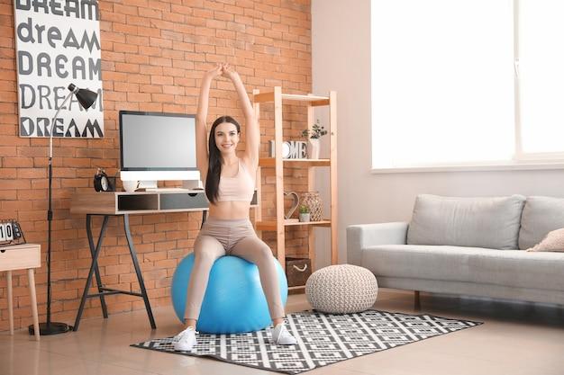 Femme faisant des exercices avec ballon de fitness à la maison