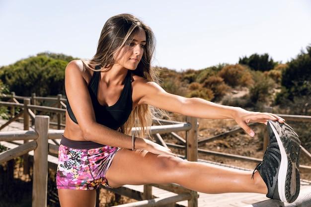 Femme faisant des exercices d'échauffement sur la jetée