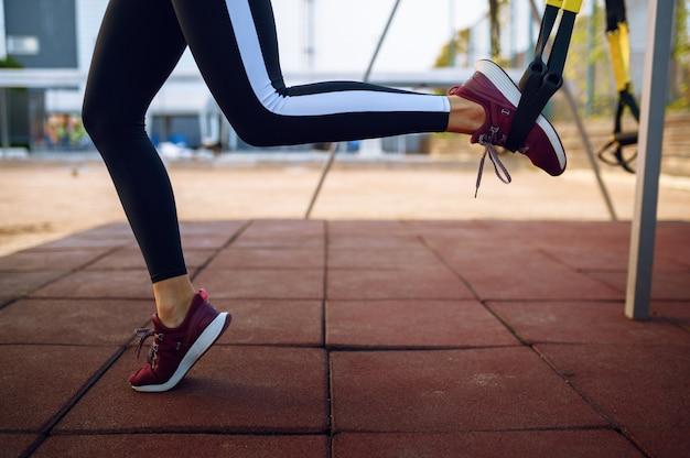 Femme faisant des exercices d'étirement avec des cordes sur un terrain de sport en plein air