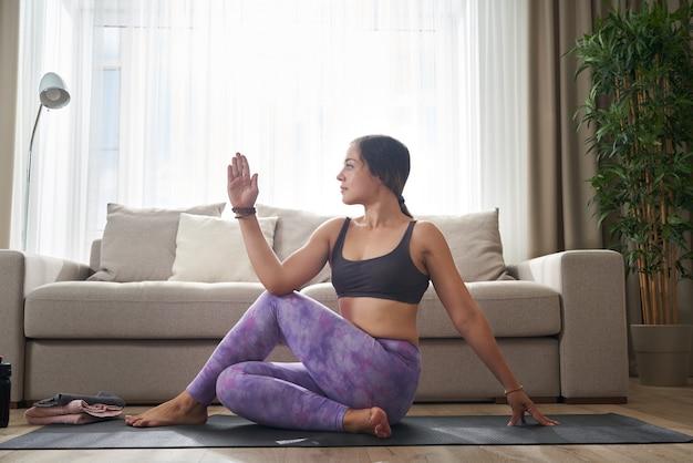 Femme faisant des exercices d'étirement du yoga assis sur un tapis près du canapé dans le salon à la maison