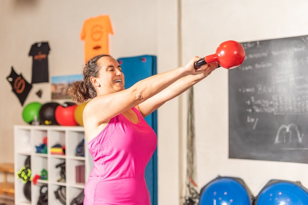 Femme faisant des exercices de swing kettlebell dans la salle de sport. concept d'exercice avec équipement en salle de sport.