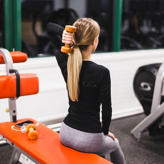 Femme faisant des exercices de triceps avec haltère