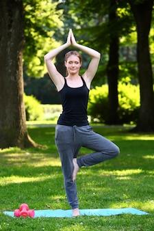 Femme faisant des exercices de yoga dans le parc