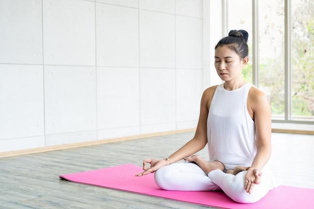 Femme faisant des exercices de yoga dans la salle de sport couverte se bouchent avec la surface.