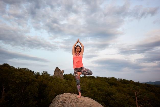 Femme faisant des exercices de yoga debout pieds nus sur une jambe sur le rocher de la grande montagne sur fond de hauts de la forêt verte le jour d'été lumineux