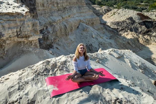 Femme faisant des exercices de yoga d'étirement sur le tapis à la carrière de sable de la nature