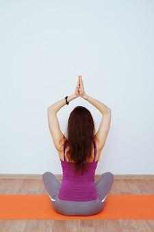 Femme faisant des exercices d'yoga sur tapis orange, qui s'étend.