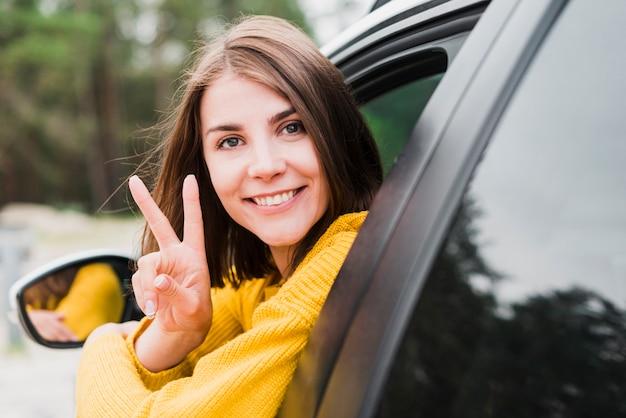 Femme faisant face à la caméra faisant signe de paix