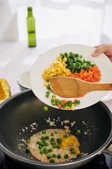 Femme faisant frire des légumes au wok