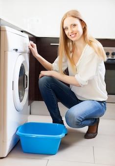 Femme faisant la lessive avec machine à laver