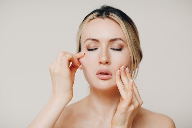 Femme faisant un massage d'auto-yoga de gymnastique faciale et des exercices pour la peau du visage.