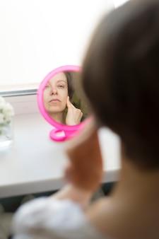 Femme faisant un massage du visage devant le miroir.