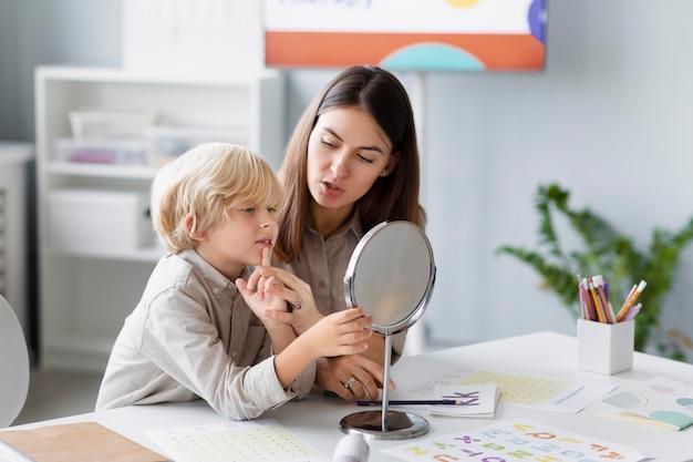 Femme faisant de l'orthophonie avec un petit garçon dans sa clinique