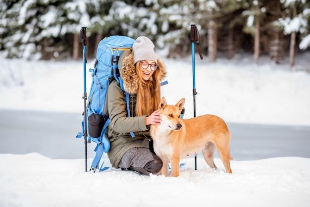 Femme faisant une pause pendant la randonnée hivernale en caressant son chien dans les montagnes enneigées près du lac et de la forêt