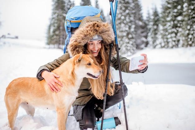 Femme faisant une pause pendant la randonnée hivernale faisant un selfie avec son chien dans les montagnes enneigées près du lac et de la forêt