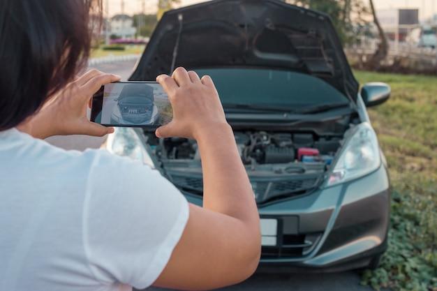Femme faisant photo au moteur de la voiture