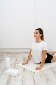 Femme faisant une pose de yoga sur un tapis blanc