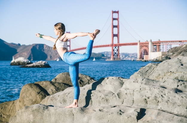 Femme faisant des poses de yoga sur une plage.