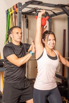 Femme faisant pression sur l'épaule avec kettlebell avec l'aide d'un entraîneur dans un club de santé. concept d'exercices avec équipement en club de santé.