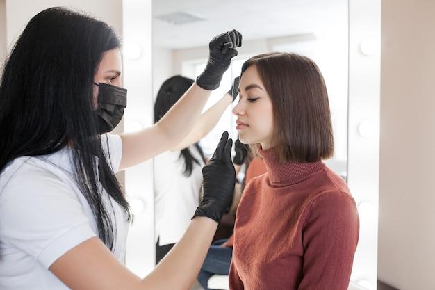 Femme faisant la procédure cosmétique des sourcils. le maître du façonnage des sourcils sert sa femme cliente.