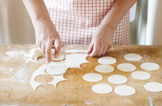 Femme faisant des raviolis, vareniks. fait main.