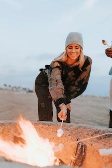 Femme faisant rôtir une guimauve sur un feu de joie