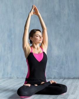 Femme faisant un salut vers le haut en position assise