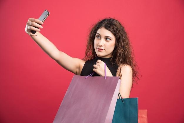 Femme faisant selfie avec des sacs sur rouge.