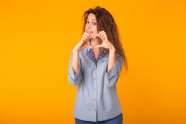 Femme faisant signe de coeur avec les mains sur jaune