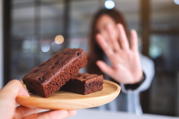 Une femme faisant signe à la main de refuser un gâteau brownie dans une assiette en bois de quelqu'un