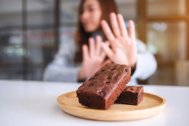 Une femme faisant signe à la main de refuser un gâteau brownie dans une assiette en bois
