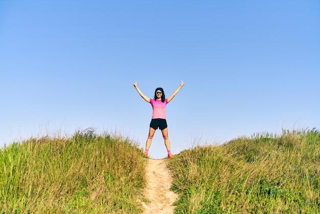 Femme faisant le signe de la victoire en haut de la piste sur un chemin droit et extensible dans un champ d'herbe.