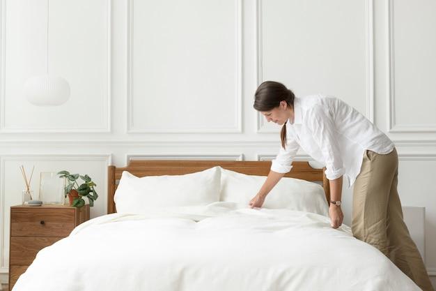 Femme faisant son lit, style intérieur scandinave