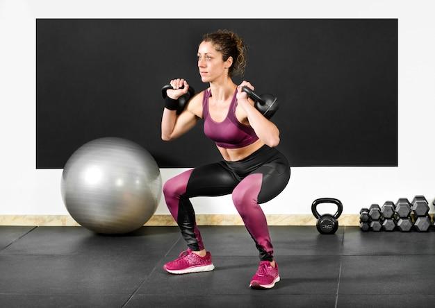 Femme faisant des squats avec des kettlebells