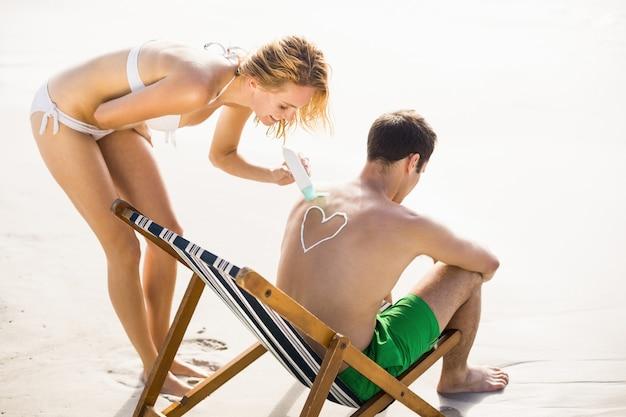 Femme faisant un symbole de coeur sur le dos de l'homme tout en appliquant une lotion écran solaire