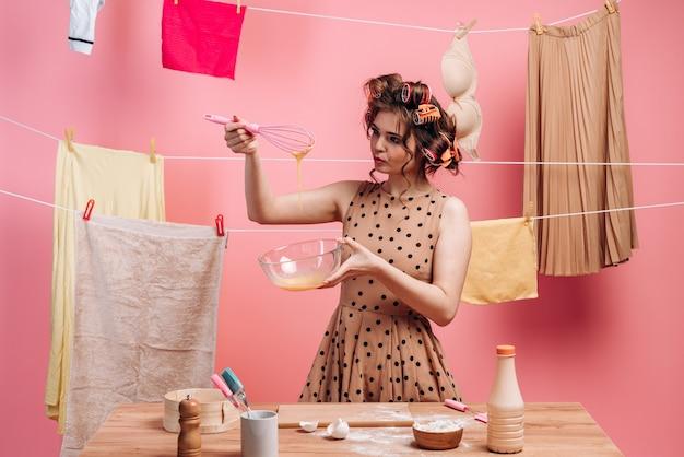 Femme faisant les tâches ménagères. sur fond de vêtements suspendus, une femme avec des bigoudis prépare de la nourriture.