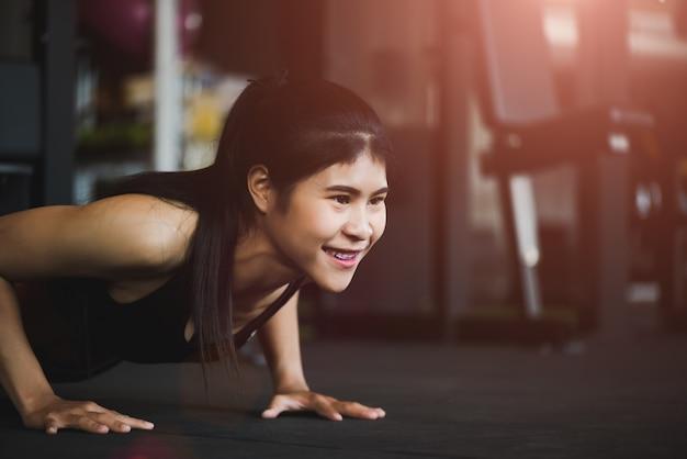 Femme faisant des tractions au gymnase. muscle, exercice et concept de mode de vie sain.