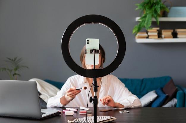 Femme faisant un vlog de maquillage avec son smartphone