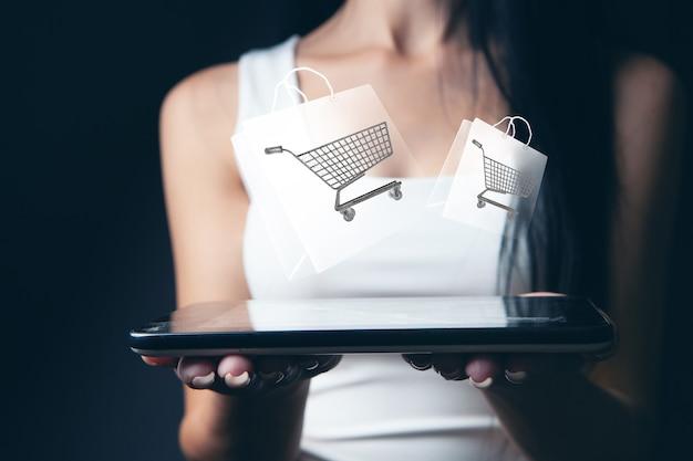 Femme fait des achats en ligne sur un panier tablet.shopping